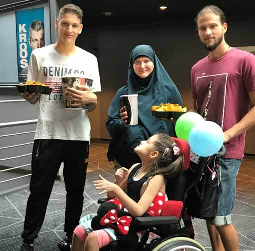 Mädchen im Rollstuhl mit Familie im Kino