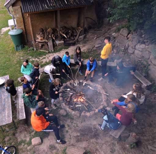 Kinder sitzen am Feuer im Kreis