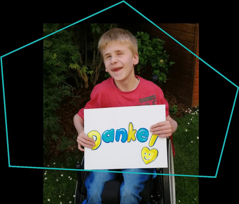 Junge im Rollstuhl mit Danke Schild