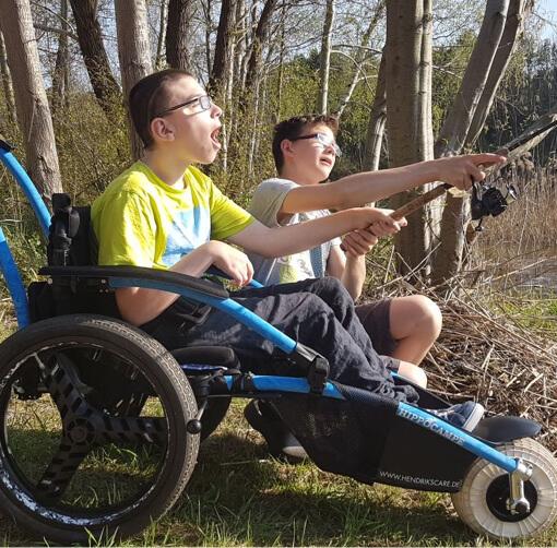 Kind mit Freund im Rollstuhl