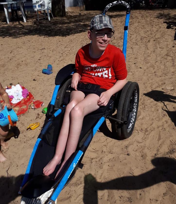 Junge im Rollstuhl am Strand