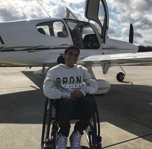 Junge im Rollstuhl auf Rollfeld