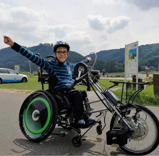 Junge freut sich über seinen Rollstuhl