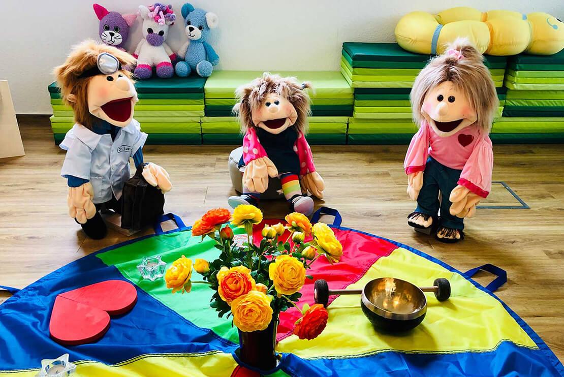 Drei Puppen sitzen in einem Kreis