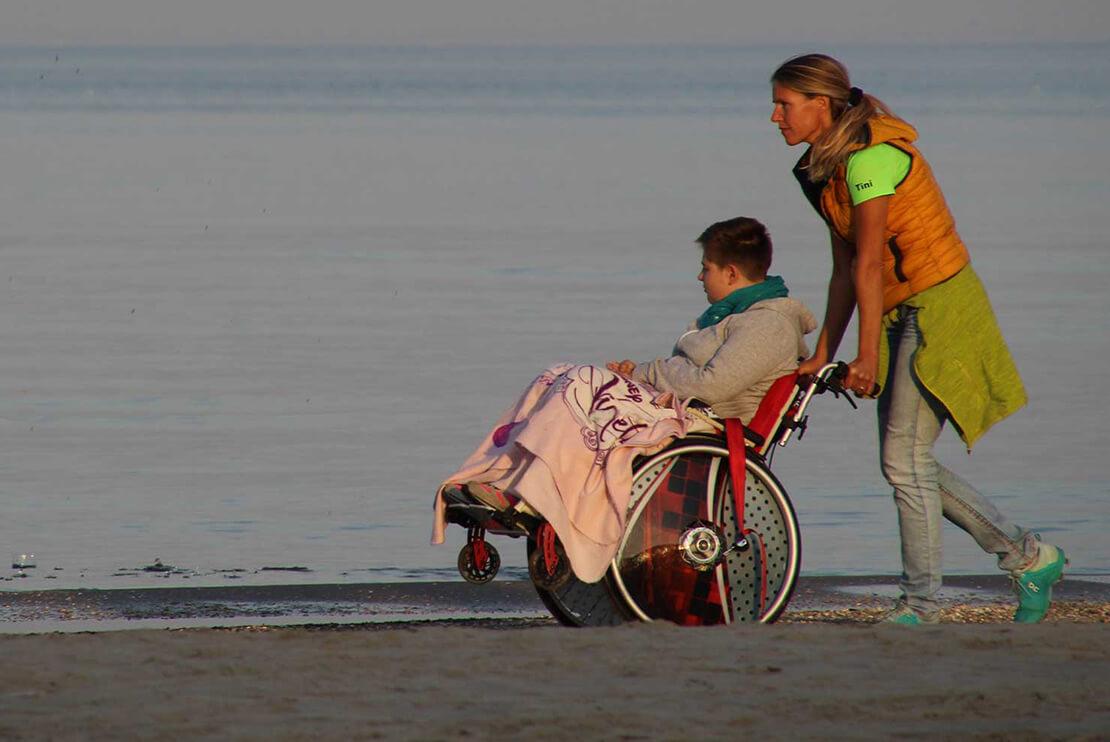 Eine Person schiebt eine andere im Rollstuhl